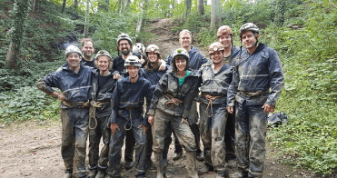 A group of 3DHubs employees in muddy climbing/spelunking gear