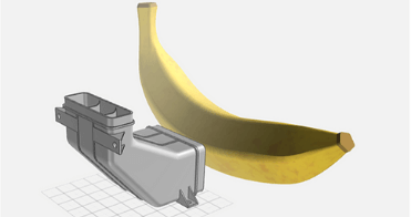 Imate of our Design for Manufacturing tool, with the banana shown for scale next to the part, which was invented during one of our innovation sprints