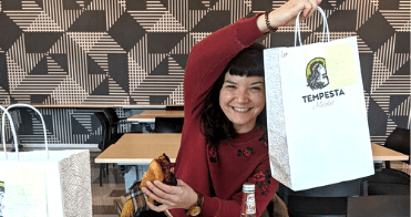 A US 3DHubs team member holding up a food delivery bag ordered through GrubHub
