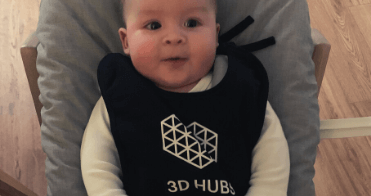 A baby wearing a bib with the 3DHubs logo on it