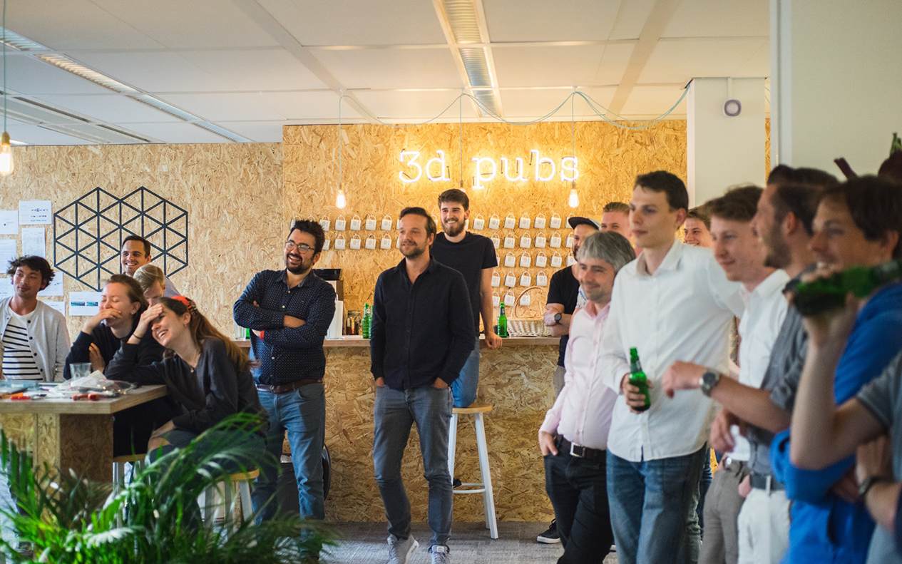 Group of 3DHubs employees gathered around with drinks